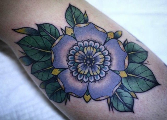 Tender traditional violet flower tattoo on arm