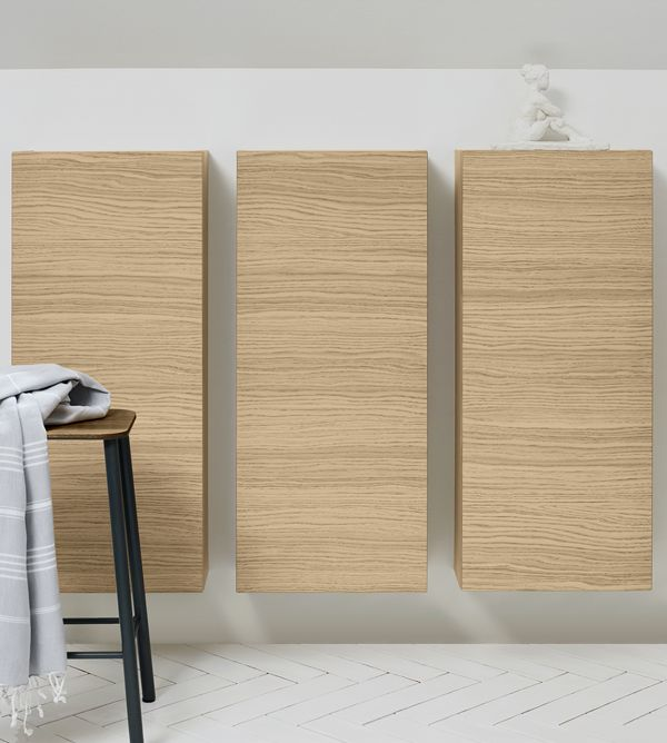 Wall cabinets cleverly mounted beneath a sloping wall, where a deeper cabinet would appear clumsy or take up too much space.