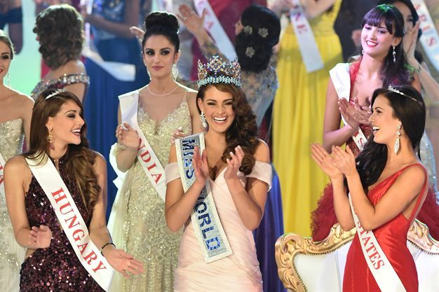 Miss South Africa and the 2014 Miss World, Rolene Strauss (C), dances with first runner up Miss Hungary Edina Kulcsar (L) and second runner up Miss United States Elizabeth Safrit (R). (Photo by AFP/Leon Neal)