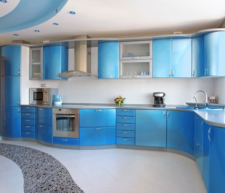 Elegant bright blue kitchen with curved cabinets and stainless steel bench