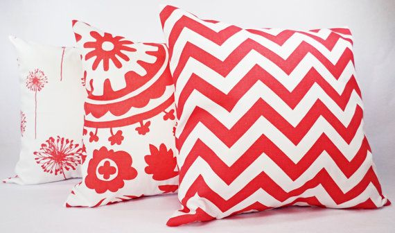 Three coral decorative throw pillows in a coral and white print. These throw pillow covers fit any size pillow insert from a 12 x 16 lumbar cover to a 26 x 26 euro sham and are 100% cotton. This listing is for a coral chevron cover, a coral suzani cover, and a coral dandelion cover.