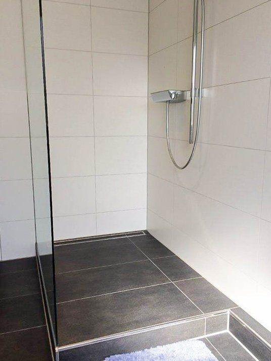 Begehbare Dusche auf einem kleinem Podest mit Glas…
