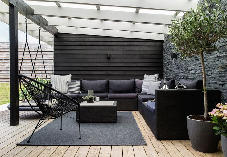 I like how you can create a chill out space within a garden and this patio looks perfect with the sofas, cushions, rug and plants.