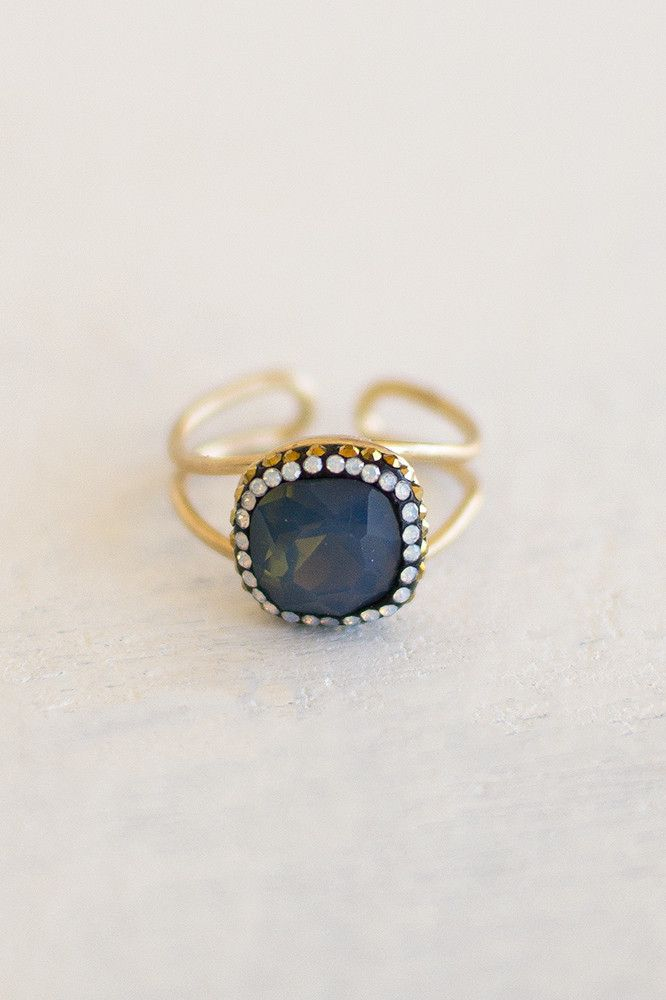 Eye-catching rings are definitely on our list of favorite things! This dark blue adjustable ring is absolutely stunning. It features a carbon colored gem encased by faux diamond studs. Double band mat