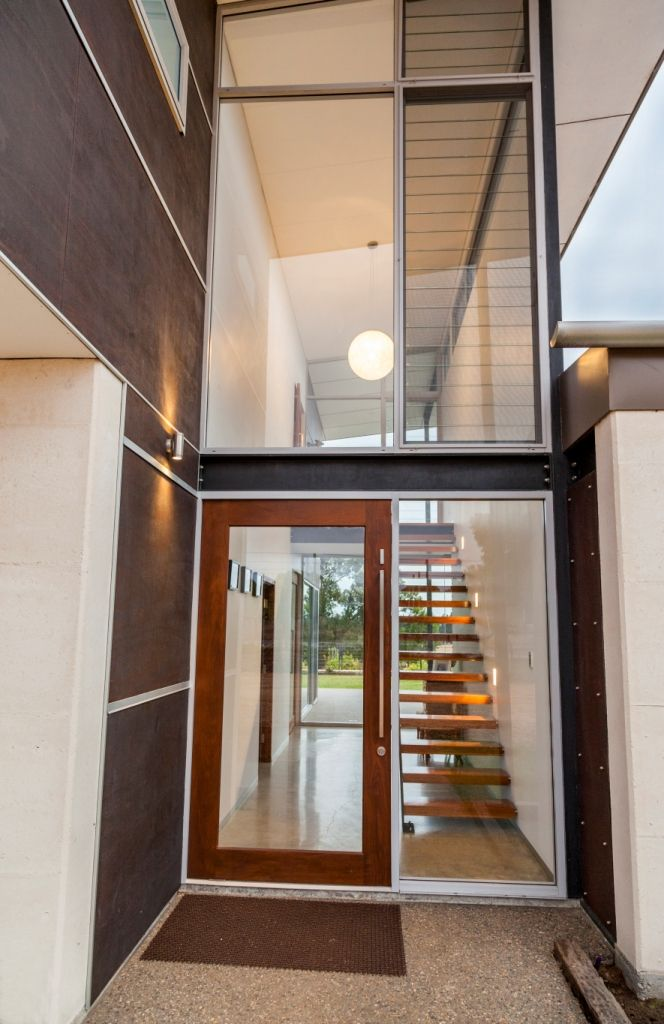 ENTRY - Breezeway glass louvres to underside of eaves lining to capture cooling breezes.  Madinoz door hardware.  Jarrah pivot door to FOYER.  Frameless glass balustrade to stair.
