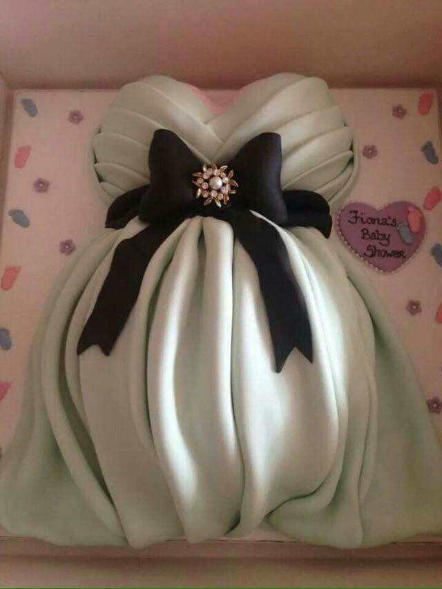Beautiful pregnant belly cake covered in green drapery and accented with a delicate black sash and added jewel