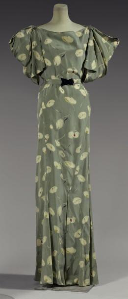 * Robe de Garden Party, 1934, modèle n°4750. Crêpe de soie imprimé, semis de fleurs abstraites ivoire sur fond vert sauge. Manches courtes à découpes donnant un effet drapé, jupe au bas prolongé de plis creux. Ceinture en tissu à fermoir en bakélite noire - Madeleine Vionnet
