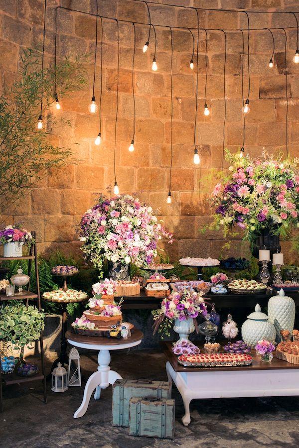 Mesa de doces rústica e romântica, com arranjos irregulares rosa, lilás, roxo, com varal de luzes, detalhes menta/verde água. Foto: Flavia Soares