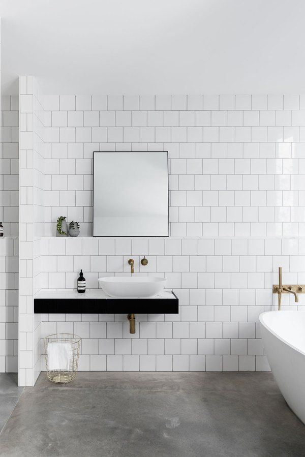 Bathroom With Bright White Subway Tile Walls And Dark Concrete