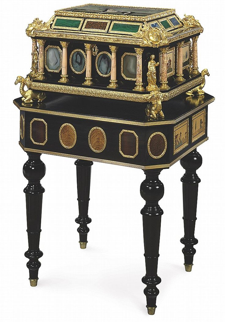 AN ORMOLU-MOUNTED PIETRA DURA AND EBONY CASKET ON LATER STAND <br />THE CASKET, FLORENCE, CIRCA 1850 AND INCORPORATING AN EARLY 18TH CENTURY PIETRA DURA PANEL, THE MOUNTS PROBABLY FRENCH<br /><br />The canted rectangular lid with a central panel of a horse in a landscape surrounded by lower hardstone panels of malachite and lapis, the corners punctuated by masks and opening to a later velvet-lined interior with hinges and lockplates engraved with foliage, the sides with engaged columns of…
