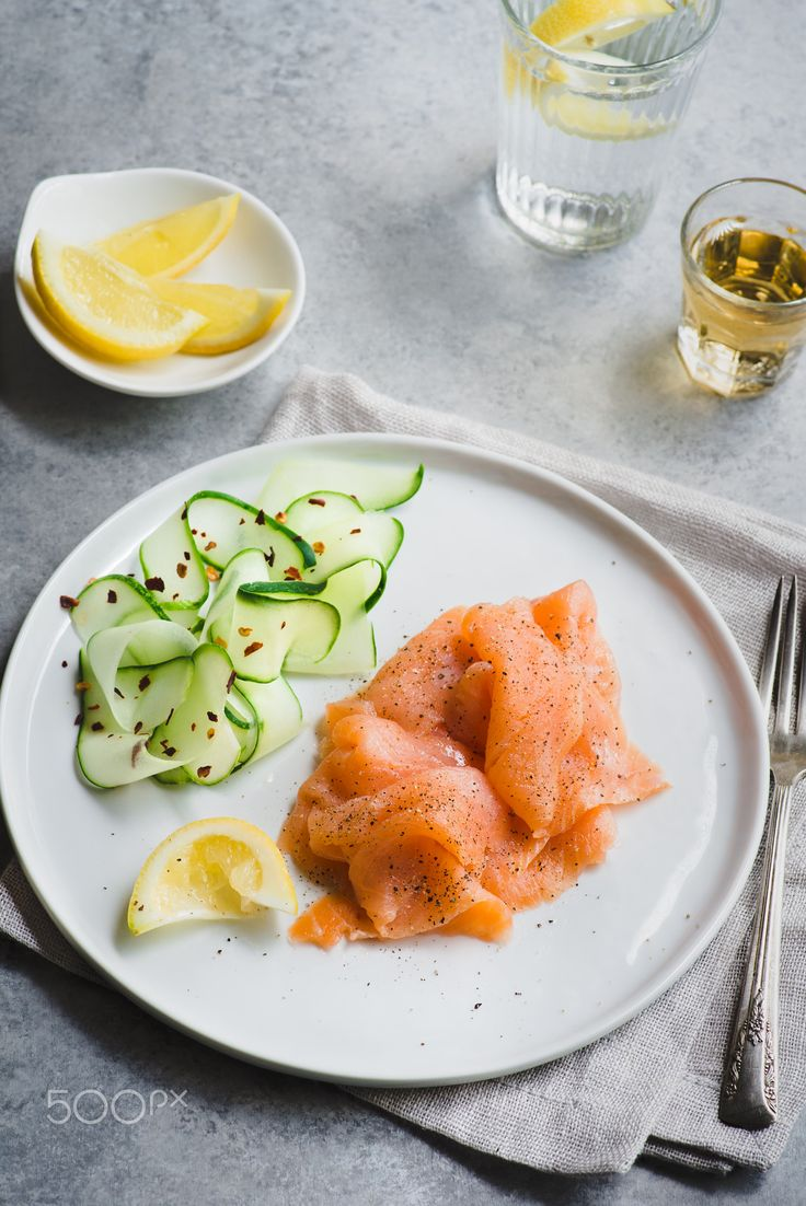 Smoked salmon with cucumber salad - Smoked salmon with cucumber salad. Cured, salted salmon. Appetizer on white plate, over grey background