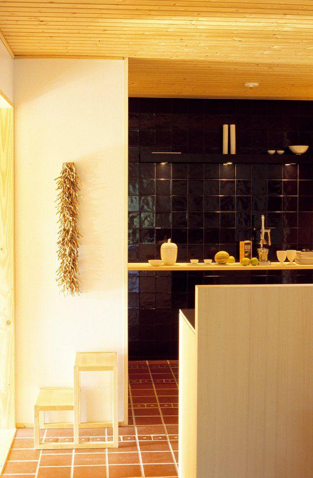 Cuisine dont un mur est tapissé de terre cuite, au sol de la céramique  et bar meuble de cuisson