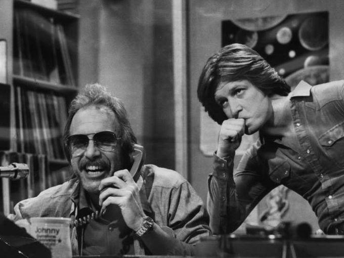 "Jan. 1979: ""WKRP in Cincinnati"" DJ Dr. Johnny Fever (Howard Hesseman) (left) talks to a caller while program director Andy Travis (Gary Sandy, center) listens in."
