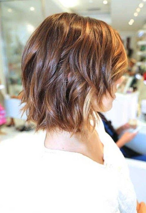 À l'arrière, les cheveux de cette femme ont été coupés au carré et légèrement dégradés. Par contre, à l'avant, le coiffeur les a coupés plus court, et a ramené les cheveux sur le côté. Toutes les pointes ont été effilées. La coloration châtaine a été éclaircie par quelques mèches plus pâles.