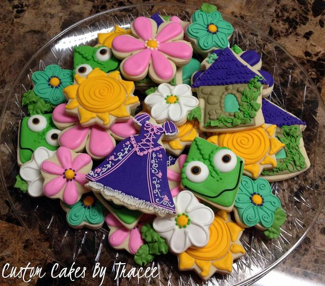 Various decorated cookies with monsters, flowers, dresses, houses.  Different Rapunzel Cookies by Custom Cakes By Tracee, via Flickr