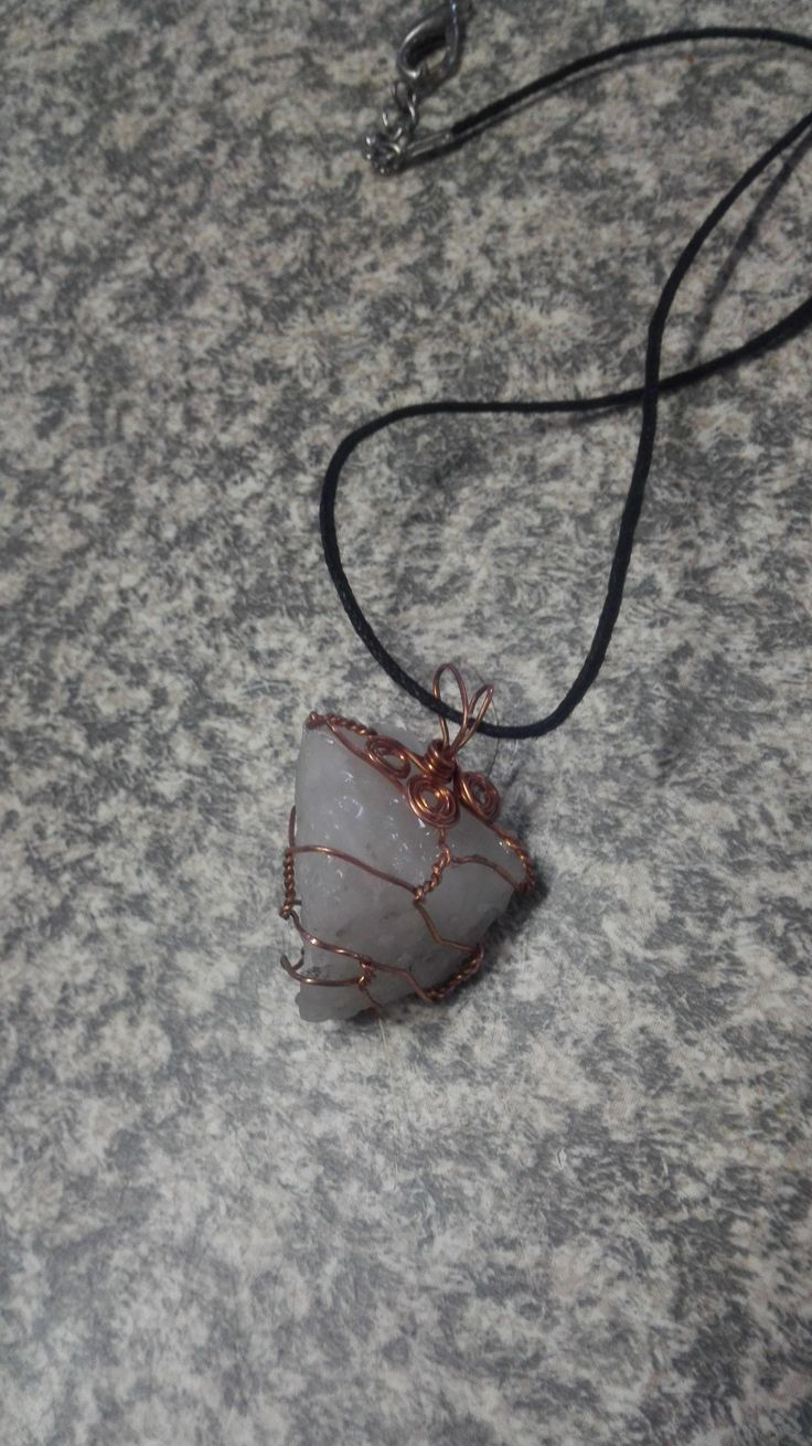 Opaque quartz crystal with copper wire wrapped around it; on a clavicle length black cord.