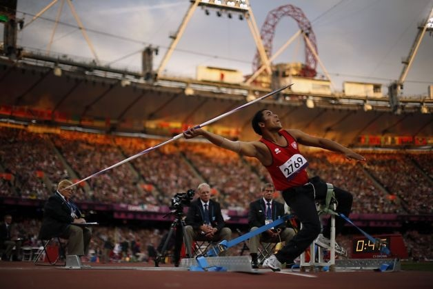 In light from the setting sun, Tunisia's Mohamed Ali Krid makes a throw in the men's javelin F34 category event during the athletics competition at the 2012 Paralympics, Saturday, Sept. 1, 2012, in London.  (AP Photo/Matt Dunham) Photo: Matt Dunham, Associated Press / SF