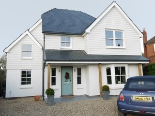 central front door sash windows porch canopy cladding slate render and gables