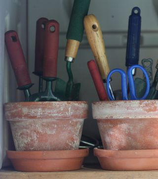 Aby at Creative Organizing uses sand-filled clay pots to store garden tools (which also keeps them dry and rust-free).
