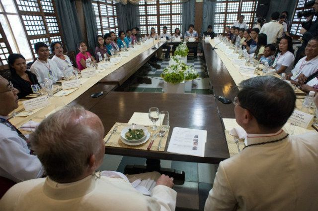 LUNCH WITH SURVIVORS. In this handout picture released by the Vatican Press Office, Pope Francis (left) shares a meal with disaster survivors in Palo, Leyte, on January 17, 2015, as part of his trip to the Philippines. Photo courtesy of Osservatore Romano/AFP