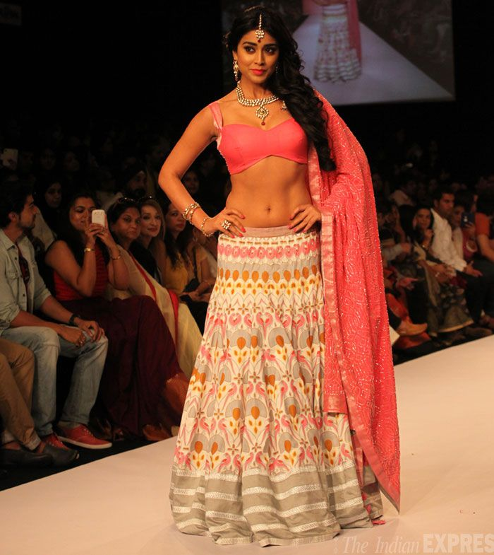 Day 4 of the ongoing Lakme Fashion Week 2013 in Mumbai saw designers Shravan Kumar, Gaurang and Shruti Sancheti among others display their stunning collections on the ramp.  Telugu actress Shriya Saran looked stunning in a lehenga-choli in the beautiful Shravan Kumar theme colours – Pink and Grey.  Even though the lehenga was dangerously low, the beauty carried off the look with elan and elegance. (IE Photo: Amit Chakravarty)