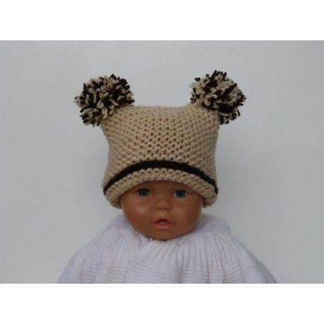 Très jolie petit bonnet rectangle pour bébé de 0 à 2 mois ou bien taille 6 mois de couleur beige & marron foncé avec une petite rayure de couleur marron sur le départ du bonnet. Ce bonnet rectangulaire est tricoté en laine acrylique épaisse et chaude. Entièrement tricoté main tout point mousse. Il se termine par deux superbes pompons mélange de marron et beige.
