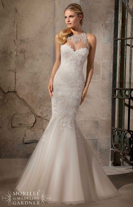 Mori Lee Bridal 2723 is a stunning mermaid dress that features intricate beading over sheer at the neckline. The back has a diamond shaped keyhole with buttons at the top and bottom.  Mori Lee Bridal 2723 has gorgeous lace and a tulle skirt.