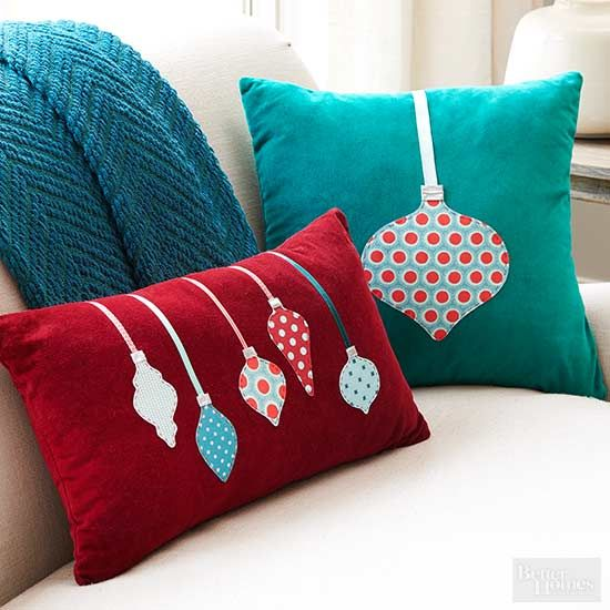 Removable pillow covers let you effortlessly transition your throw pillows from season to season. For the Christmas edition, cut scraps of assorted fabric into ornament shapes, and use iron-on medium weight interfacing to secure them to the pillow front, stitching on ribbon as shown./