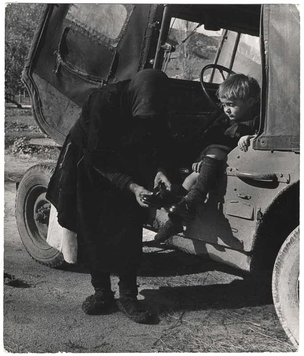 [Elefteria sitting on a jeep while a woman puts on her new pair of shoes, Oxia, Greece]-David Seymour,1949