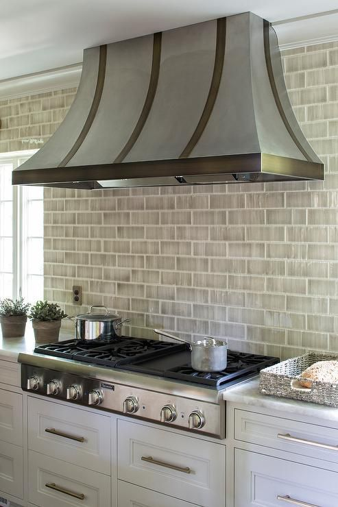 A stainless steel French range hood is mounted to gray brick backsplash tiles above a stainless steel integrated gas cooktop fixed to white drawers finished with brushed nickel pulls and a white onyx countertop.
