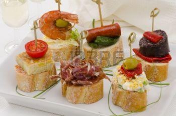 Pan Montaditos cocina espa�ola en rodajas cubierta con una gran variedad de aperitivos Tapas espa�olas Dos vasos de vino de Jerez en el fondo photo