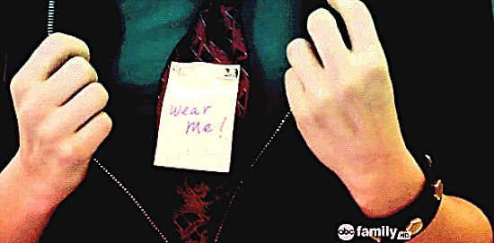 """Pretty Little Liars, 1x15, """"If at First You Don't Succeed, Lie, Lie Again,"""" aired 31 Jan. 2011. Aria Montgomery (Lucy Hale). Aria un-zippers her jacket to show a note pinned to her tie that says 'Wear me!' Aria: """"So I know I'm on the right track?"""" Ezra Fitz, played by Ian Harding: """"Okay."""" Aria hands Ezra her workbook with the words 'Tomorrow night?' written on the page and a ticket to the Philadelphia Museum taped to the page. Aria: """"What do you think of my work so far?"""""""
