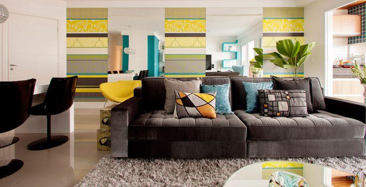 Sofá de tecido liso escuro, mesa central de resina com tampo de espelho, piso de porcelanato cinza e tapete felpudo completam a decoração da sala de TV.