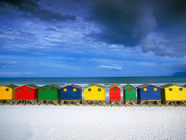 Brilliantly colored beach huts draw a line in the white sand of Muizenberg, South Africa.