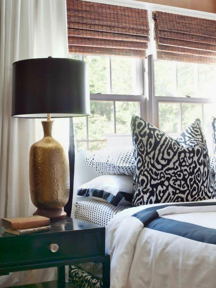 chambre à coucher avec une literie en blanc et bleu, une lampe de chevet en noir et or et stores bambou romains