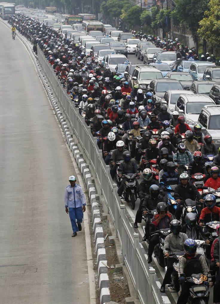 A man walks in a bus lane next to a morning rush hour traffic jam in Jakarta, Indonesia. (Reuters)