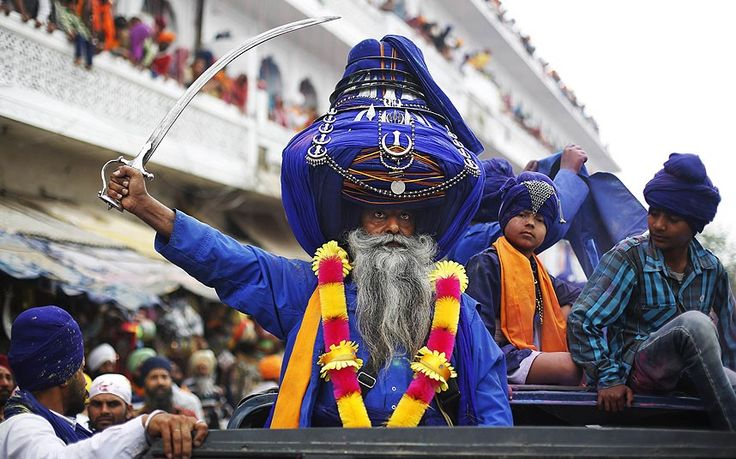 Sikh warrior Major Singh, wearing a 425 metre long turban, brandishes a sword as he participates in a religious procession.
