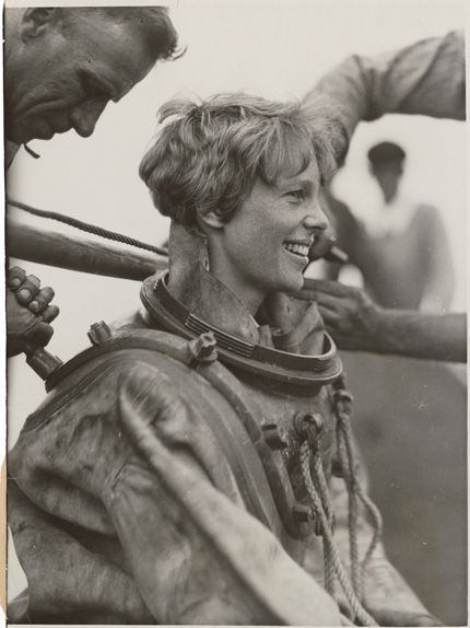 Amelia Earhart is helped out of her deep sea diving suit after exploring the bottom of the sea off Block Island, Rhode Island. July 25, 1929.