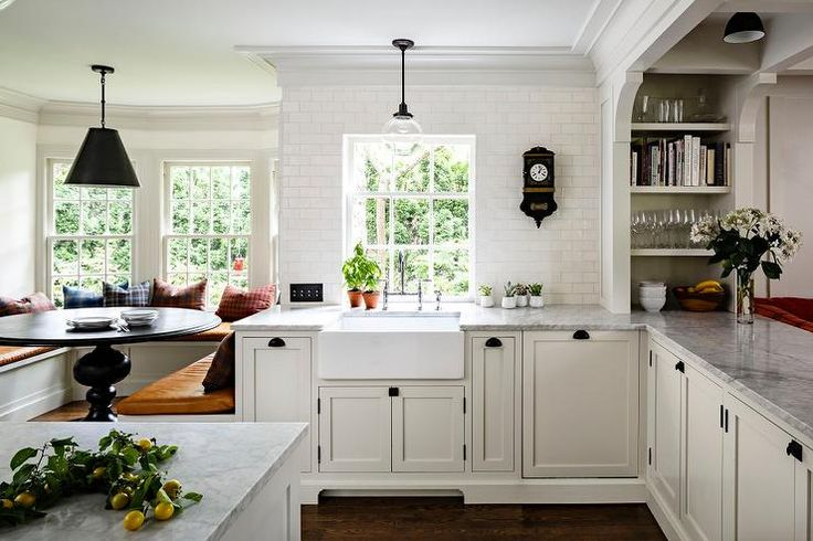 Lovely kitchen features ivory shaker cabinets accented with oil rubbed bronze cup pulls and latches paired with gray marble countertops and a white glazed mini subway tiled backsplash.