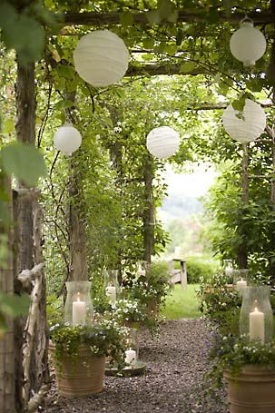 Love this for garden parties! White paper lanterns and white pillar candles & hurricanes sitting in annual pots.
