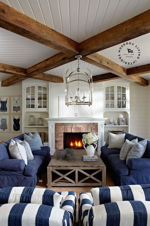 White and blue living room with beadboard clad ceiling adorned with a polished nickel lantern pendant mounted in the center of criss cross ceiling beams. The living room features a set of framed vintage swimsuits to the left of a beadboard planked fireplace and built-in cabinets with red brick surround and barn style doors above the mantle which conceal the tv. A pair of denim blue sofas layered with pillows stand face to face across from a large gray wash coffee table
