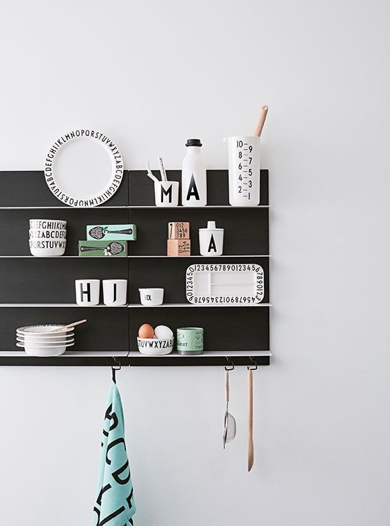 Paper Shelves put together in the kitchen to create a storage wall. A practical, graphic and personal solution for kitchen design.