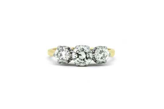 Trilogy Rings are the ultimate declaration of love, and this vintage champagne diamond ring is no exception! This holy trinity of diamonds carries a meaning that has held strong for many centuries; You are my past, my present, and my future. Handcrafted in 18ct Gold, the three brilliant diamonds are held in a lavish platinum setting studded with heart shaped scrolls and a gently tapered ring band that lets the diamonds do all the talking. Speaking of diamonds, this ring has 1.22cts of super…