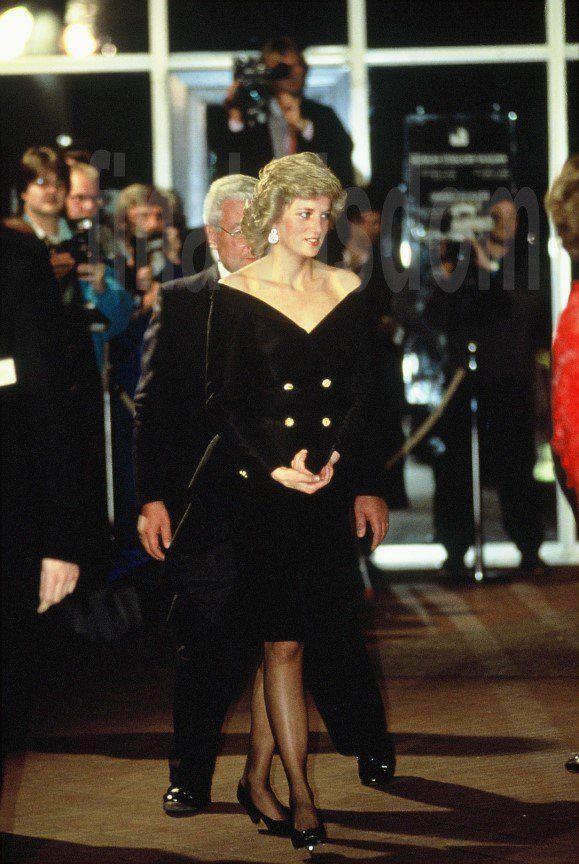 Diana....je trouve cette photo MYSTIQUE.   Il nous faut la regarder 2x pour la comprendre.... Les mains de Lady Di en avant sur son abdomen et deux autres mains sur ses hanches..... surprise le Monsieur la suivant de près habillé en noir nous joue un tour avec ses mains....  ha! Ha!