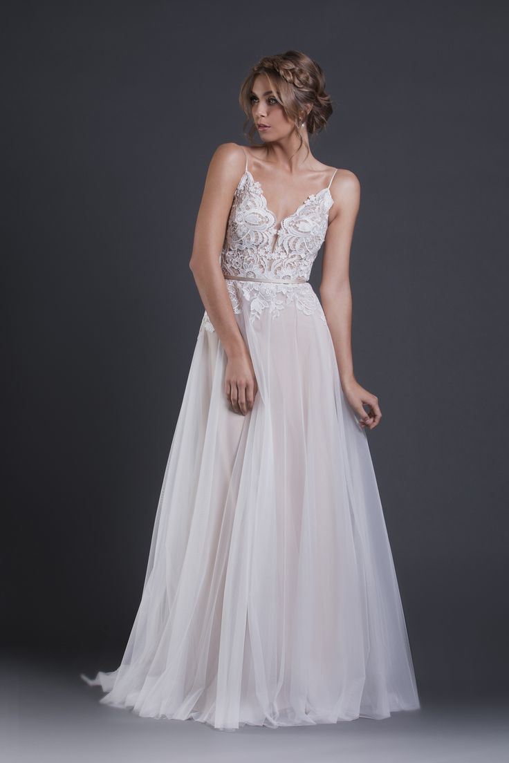 A structured style gown with a sheer bodice of guipure lace, featuring narrow spaghetti straps and a deep V-neckline. Hand stitched lace trickles down from the bodice into the full tulle skirt.  The waist is finished with a narrow sash.  Colours Available: Champagne/Cream (As shown), Cream.