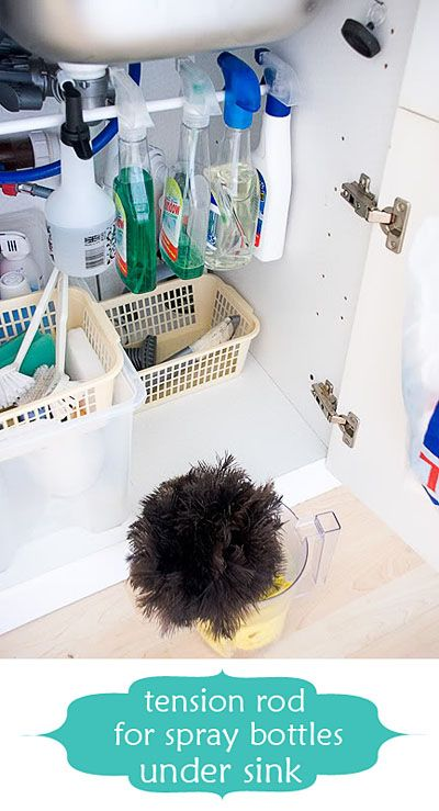 Hang spray bottles from a tension rod under the sink.