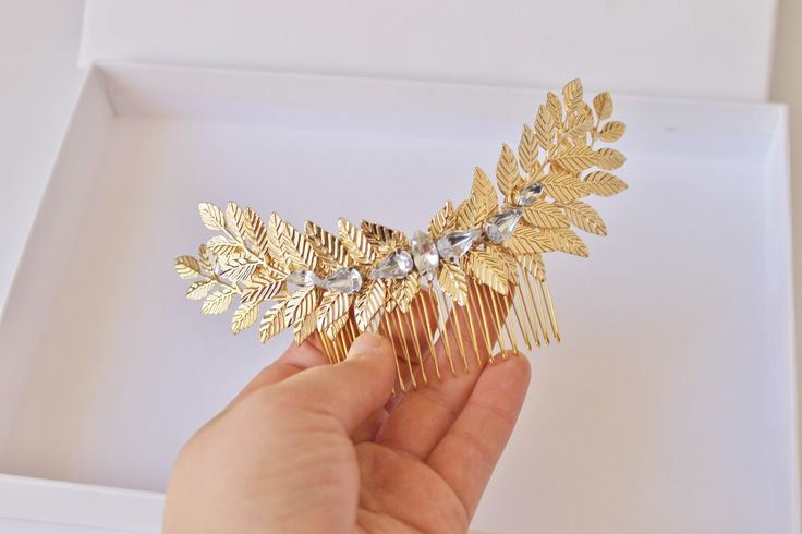 """Grecian shiny Gold tone laurel leaf hair bridal combThis gold-plated comb is embellished with multiple gorgeous shiny gold tone branches which are embellished with sparkling crystals. This hair comb can be worn at the back of an up-door on the on the side of the head, complementing many hairstyles.Measures 7"""" x 1.5"""" (widest point of leaves - not including comb)Set on a gold-plated wire hair comb, this hair piece is as comfortable as it is elegant.A perfect addition to a bohemian bridal…"""