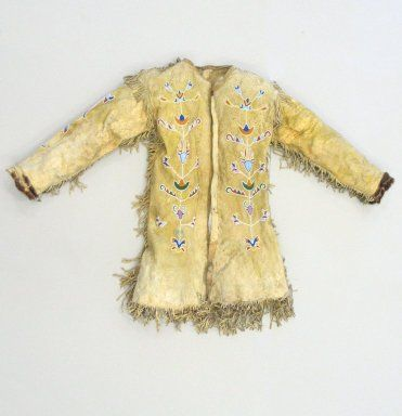Red River Metis . Man's Shirt Cut in European Style, early 20th century. Buckskin, pigment, fur, colored glass, gilt and silver, cotton cloth, pigment, at shoulders.  probably Metis or Santee  made in the late 1800s. Style derived from Red River Métis. Beadwork has long, spidery look i.e. Crow design where the flower sets in. So may be a mix- Métis inspired Eastern Sioux or Crow. Collar was originally navy blue now faded.
