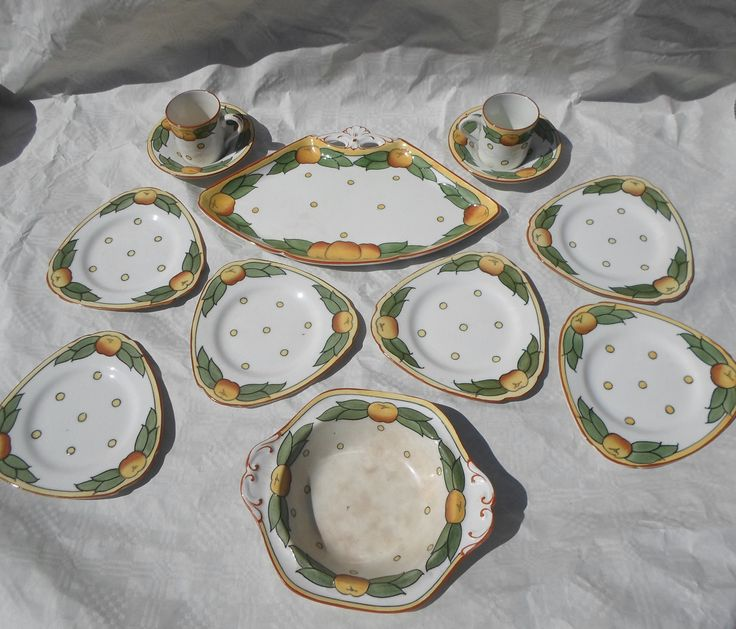 A 1920s Burleigh Ware sandwich set, designed by Charlotte Rhead in the 4105 Garland pattern, comprising a fan-shaped dish, six triangular plates, a bowl and two coffee cans & sauces, featuring a tube-lined decoration of oranges and leaves, printed marks to bases