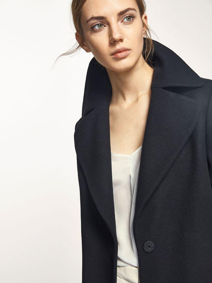 Abrigo negro con detalle de bolsillos en piel, confeccionado en una delicada mezcla de lana. Corte recto, cuello con solapas de muesca, cierre mediante dos botones de snap ocultos, dos bolsillos de ojal laterales, manga larga, una abertura en la parte posterior, forro y un bolsillo interior. El largo de la espalda en la talla 38 es de 90 cm.